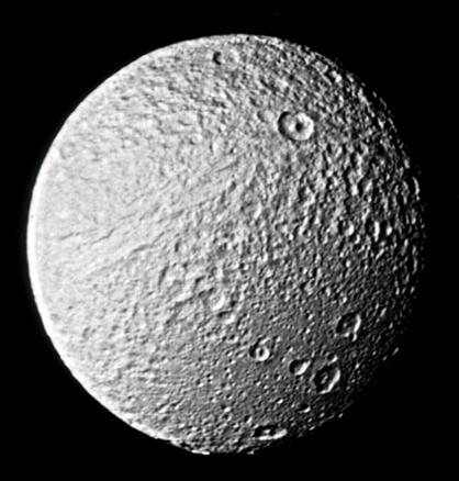 Le satellite Thetys vu par la sonde Voyager 2 en 1981. On voit sur la moitié supérieure de l\'image une énorme faille. Elle a plusieurs kilomètres de profondeur. Elle pourrait être due à un craquement de la surface déjà solidifiée de Téthys survenu lorsque l\'intérieur du satellite refroidissait et que le diamètre global du satellite diminuait.