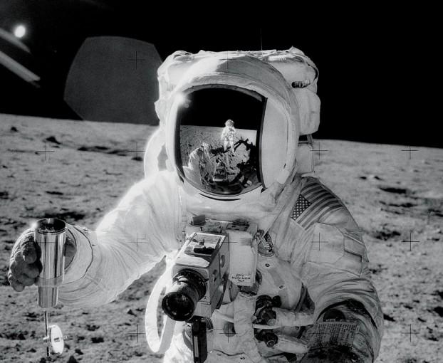 Vous reprendrez bien un peu de technologie lunaire ? L\'astronaute Alan Bean récoltant des échantillons de surface lunaire en 1969. Se reflétant sur sa visière, le photographe, Charles Conrad.
