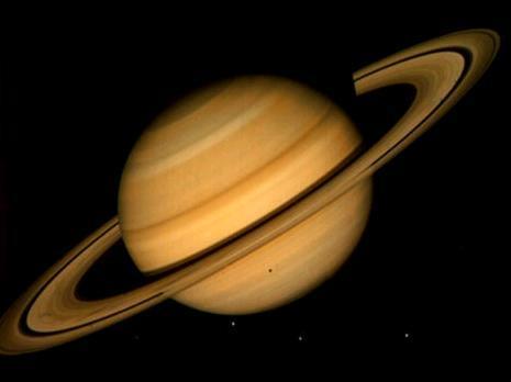 Saturne vue depuis une distance de 21 millions de kilomètres en 1981 par la sonde Voyager 2. C\'est une image en vraies couleurs. On peut voir quatre des satellites de Saturne: Téthys, Dioné, Rhéa, et (moins évident à repérer) Mimas. L\'ombre portée sur la planète est celle de Téthys.