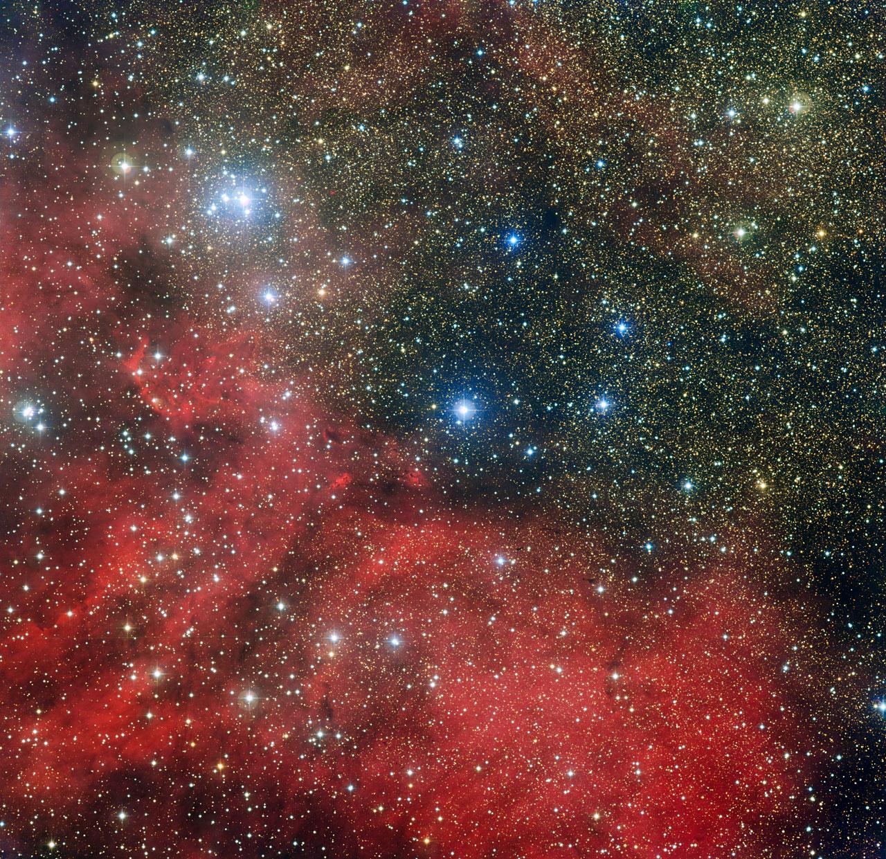 L\'amas d\'étoiles NGC 6604 est dévoilé sur cette nouvelle image prise avec la caméra WFI installée sur le télescope MPG/ESO de 2,2 mètres de l\'Observatoire La Silla au Chili. NGC 6604 est le groupement lumineux qui s\'étend en haut à gauche de l\'image. C\'est un jeune amas d\'étoiles qui constitue la partie la plus dense d\'un groupe plus largement étendu contenant environ une centaine d\'étoiles bleuâtres lumineuses. L\'image montre également la nébuleuse associée à cet amas – un nuage d\'hydrogène ionisé lumineux appelé Sh2-54 - ainsi que des nuages de poussière.