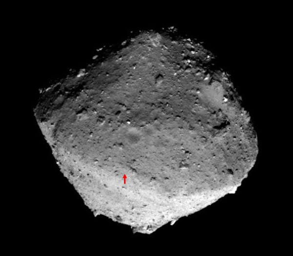 L\'hémisphère nord de l\'astéroïde Ryugu photographié le 24 janvier 2019, la flèche rouge désigne le site de contact